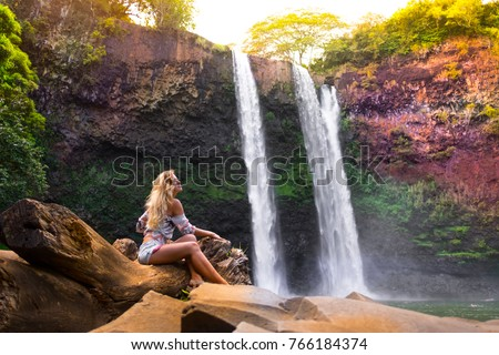 alone traveler woman seats with her back at stone and looks at colorful Hawaiian waterfall. hawaii. traveling stock photo