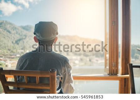 Alone traveller sitting at cafe and look out window with beautiful lake view in morning, Relax time concept #545961853