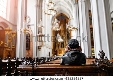 Alone woman sits on the bench in the church