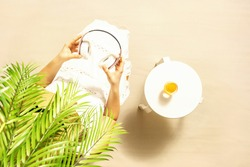 Alone woman sitting under palm tree branches. Glass of orange juice and headphones on the table. Female relaxation on the sandy beach at summer vacation. Top view