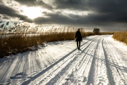 Alone woman walking on road with snow in winter, landscape, romantic scene before sunset with dark sky