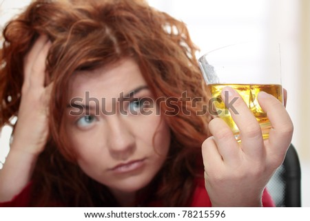 Alone young woman in depression, drinking alcohol (bourbon)
