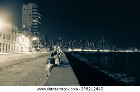 Along the Malecon, Havana, Cuba, people blurred in long exposure out at night in warm sea air sitting on sea wall across from the colonial buildings with the more modern city lights in distance.