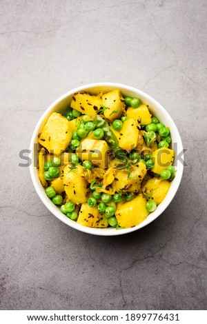 Aloo Mutter or Matar aalu dry sabzi, Indian Potato and green Peas fried together with spices and garnished with coriander leaves. served with roti or chapati Foto stock ©
