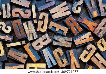 alphabet background - vintage letterpress wood printing blocks placed randomly on a grunge metal tray