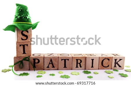 "Alphabet blocks arranged to spell ""St. Patrick,"" adorned with sparkly shamrocks and a green hat.  Isolated on white with space for your text."
