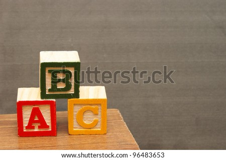 Alphabet blocks in front of the chalkboard for learning the basics of the english language.