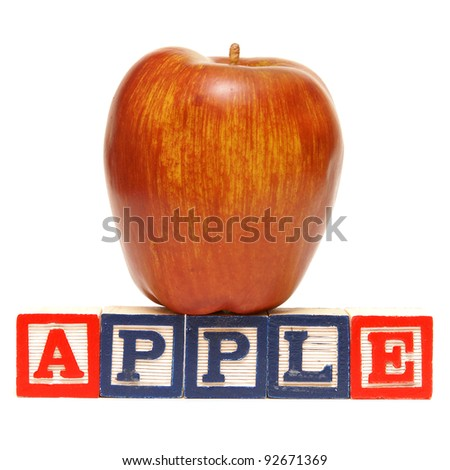 Alphabet blocks spell out the word apple with the healthy fruit being displayed.