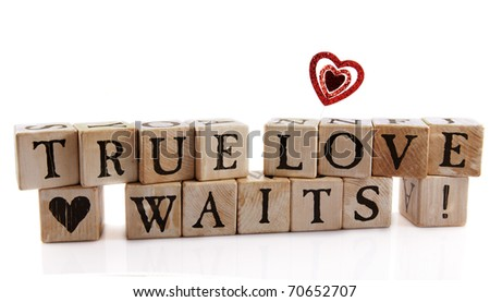 "Alphabet blocks that spell out ""True Love Waits!"" with a supporting heart block and a glittery red one floating above.  Isolated on white."