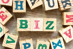 Alphabet letter block in word biz (abbreviation of business) with another on wood background