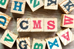 Alphabet letter block in word CMS (Abbreviation of Content management system) with another on wood background