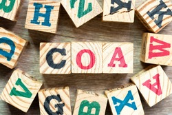 Alphabet letter block in word COA (abbreviation of certificate of analysis, certificate of authenticity, cause of action) with another on wood background
