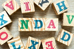Alphabet letter block in word NDA (Abbreviation of Non disclosure agreement) with another on wood background