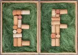 Alphabet letter E and  F made of  wine corks on green background in wooden box. ABC set
