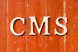 Alphabet letter in word CMS (Abbreviation of Content management system) on old red color wood plate background
