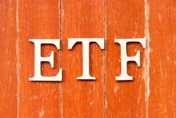Alphabet letter in word ETF (abbreviation of Exchange Traded Fund) on old red color wood plate background
