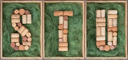 Alphabet letter S T U  made of  wine corks on green background in wooden box. ABC set