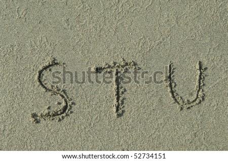 alphabet letters s t u handwritten in sand on beach