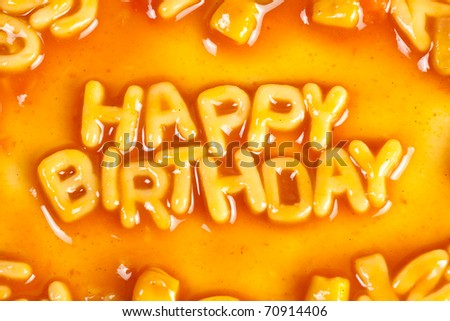 Alphabet shaped pasta forming HAPPY BIRTHDAY in tomato sauce