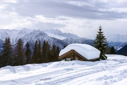 Alpine chalet sunk in deep snow in winter with thick snow on roof in the Swiss Alps, Switzerland