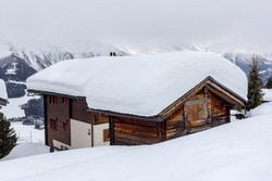 Alpine chalet sunk in deep snow in winter with thick snow on roof in the Swiss Apls, Switzerland
