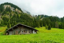 alpine farmhouse, wooden house on steep meadow, steep slope in Bonder valley, Adelboden, Switzerland