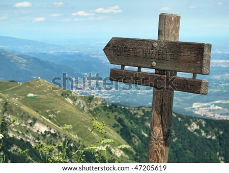 Alpine hiking trails hint along a trail. On background, hills and plains. - stock photo