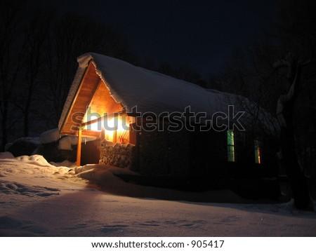 alpine hut in the snow at night