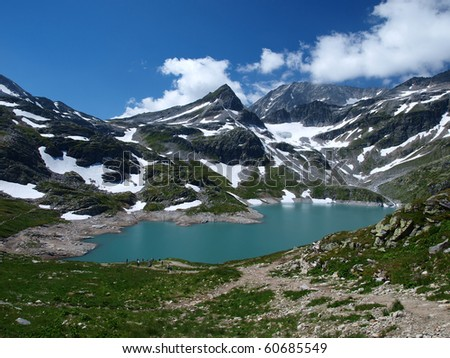 Alpine lake as a permanent element in the high mountains - stock photo