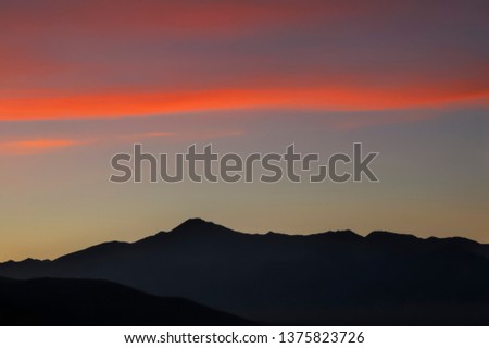 alpine landscape at sunset, red clouds in the pale sky, distant mountain range covered with evening haze, Mongolia
