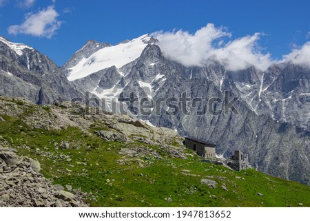 Alpine landscape near refuge Mandrone Citta di Trento. Bristly dark rocks with a glacier and clouds. At the base of the mountains a small dilapidated building. Basin Mandrone, Adamello group, Italy Foto d'archivio ©