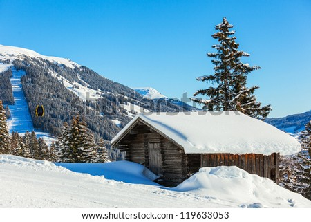 Alpine landscape. Snow-covered house, ski lift chairs, mountains. Tyrol, Austria