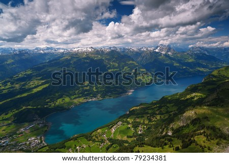 Alpine landscape, turquoise lake in mountains of Switzerland under dramatic clouds. Walensee lake panoramic view, popular touristic destination.