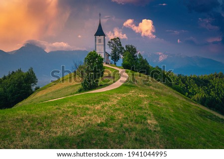 Alpine landscape with church and rural road on the mountain ridge. Colorful sunset landscape and cute Saint Primoz church with high mountains in background, Jamnik village, Slovenia, Europe Zdjęcia stock ©
