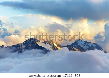 alpine landscape with peaks covered by snow and clouds #171114806