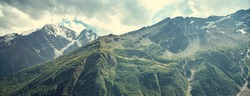 alpine landscape with peaks covered by snow and clouds. natural mountain background. vintage toning and retro stylization