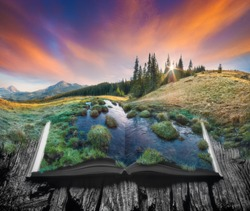 Alpine mountain valley with majestic clound in a sky on the pages of an open magical book. Majestic landscape. Nature concept.