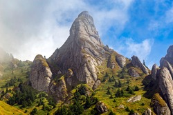 Alpine scenery with dramatic sky of Ciucas massif, part of Carpathian Mountains (view of Tigaile Mari rock formation). Photo taken on 5th of September 2020 in the Carpathian Mountains, Romania.