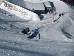 Alpine skier doing a high speed turn on a steep slope