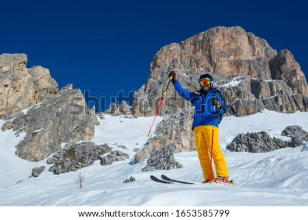 Alpine skier stand on slope in winter mountains Dolomities Italy in beautiful alps Cortina d'Ampezzo Cinque torri mountain peaks famous landscape skiing resort area Foto stock ©