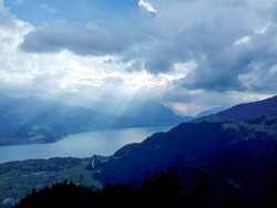 Alpine valley in a thunderstorm, interlaken, Switzerland, rain, bad weather, sun rays through the clouds, a wall of rain over the lake, clouds, green valley and mountains