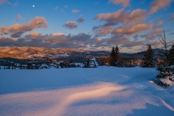 Alpine village outskirts in last evening sunset sun light. Winter snowy hills and fir trees. Picturesque clouds and Moon in dusk sky.