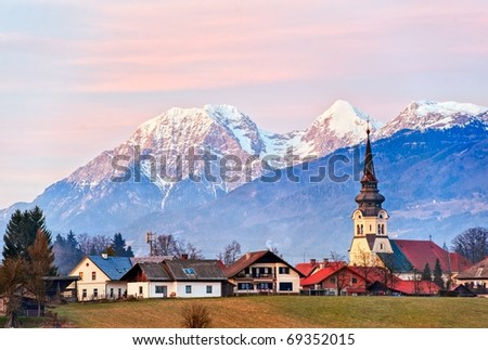 Alpine village with a church tower with snow covered mountains in background on sunset