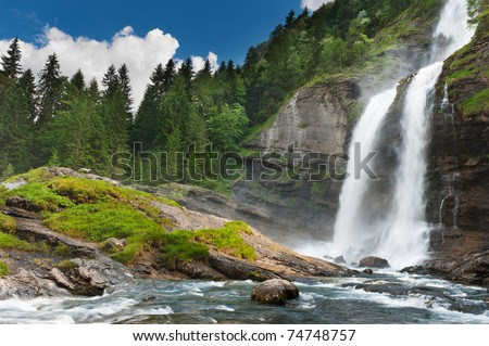 Alpine waterfall in mountain forest under blue sky. #74748757