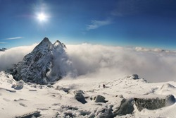 Alpinist climbing on Rysy mountain peak over clouds in High Tatras with clear blue sky and  on background