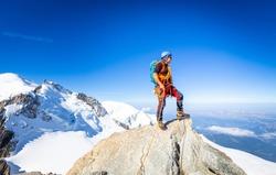 Alpinist guy mountaineer man standing posing Mont Blanc du Tacul snow mountain summit. Chamonix valley view beautiful landscape, Europe France Alps range tourism.