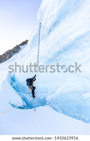Alpinist mountaineer ascent ladder over ice snow crevasse crack, extreme sport  mountain climbing. Mont Blanc massif, Europe travel tourism. #1450623956