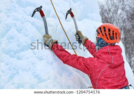 Alpinist woman with  ice tools axe in orange helmet climbing a large wall of ice. Outdoor Sports Portrait