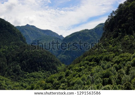 Alps in cloudy day. Alpine nature  landscape. Secluded valley between mountain forests. Iconic photo of virgin environment featuring summits, peaks and abrupt hill slopes under blue sky with clouds. #1291563586