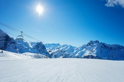 Alps mountain peaks and clean empty ski trails in Pralognan-la-Vanoise range over snowy tops